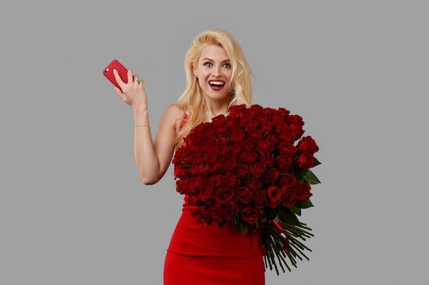 Giovane donna bionda felice che tiene un grande mazzo di rose rosse come regalo per l'8 marzo o il biglietto di s. valentino.