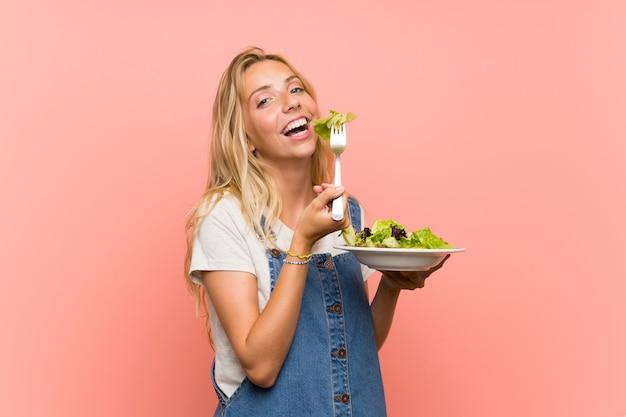 Giovane donna bionda felice con insalata sopra la parete rosa isolata
