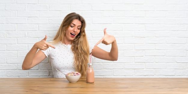 Giovane donna bionda felice con la ciotola di cereali