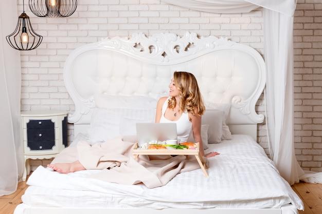 Giovane donna bionda graziosa che si siede sul letto con il computer portatile che mangia prima colazione, free lance o blogger a casa. la donna lavora al computer da casa.