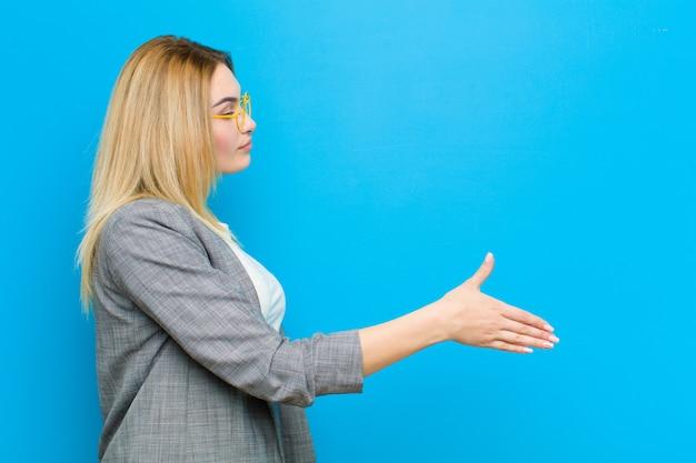 Giovane donna bionda graziosa che sorride, vi accoglie e offre una stretta di mano per chiudere un affare riuscito, concetto di cooperazione contro la parete piana
