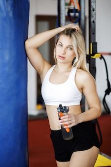 Giovane donna bionda graziosa che sta in una palestra vicino ad un pera di pugilato e che tiene una bottiglia di acqua in sue mani. stile di vita attivo. sport in palestra.