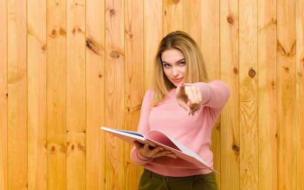 Giovane donna bionda graziosa con i libri contro la parete di legno