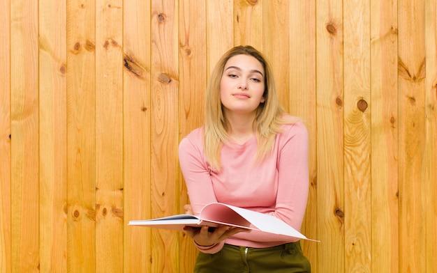 Giovane donna bionda graziosa con la parete di legno dei libri