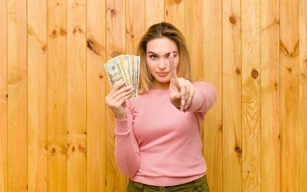 Giovane donna bionda graziosa con le banconote del dollaro contro la parete di legno