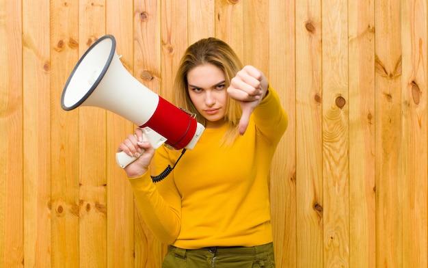 Giovane donna bionda graziosa con un megafono