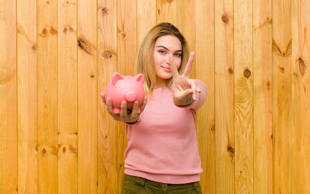 Giovane donna bionda graziosa con un salvadanaio contro la parete di legno