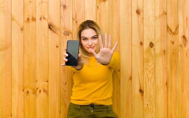 Giovane donna bionda graziosa con un telefono cellulare contro la parete di legno