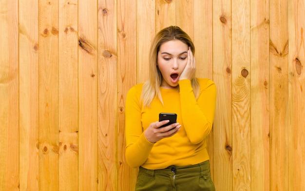 Giovane donna bionda graziosa con un telefono cellulare sulla parete di legno