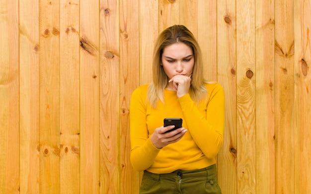 Giovane donna bionda graziosa con un telefono cellulare