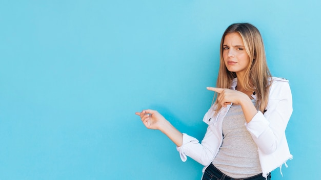 Giovane donna bionda graziosa dubbiosa che indica le dita per parteggiare contro fondo blu