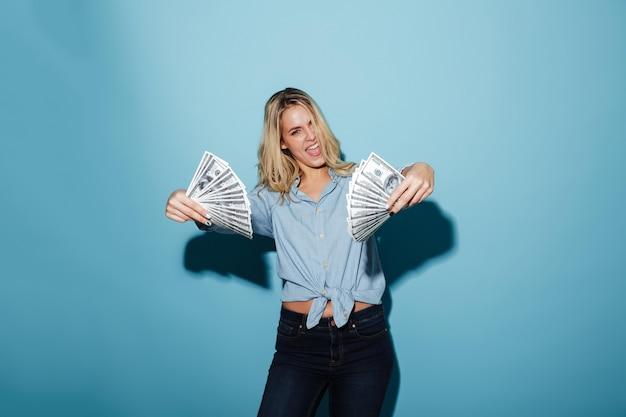 Giovane donna bionda graziosa emozionante che tiene soldi in mani.