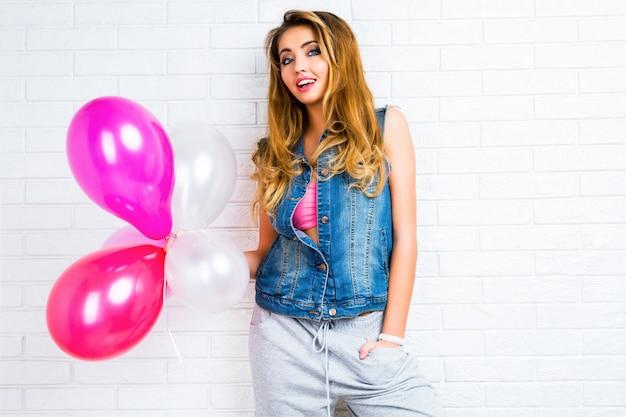 Giovane donna bionda graziosa piuttosto elegante in posa con palloncini grande festa indossando giacca di jeans hipster e pantaloni grigi sportivi