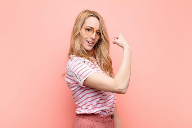 Giovane donna bionda graziosa sentirsi felice, soddisfatto e potente, flettendo in forma e bicipiti muscolari, guardando forte dopo la palestra sulla parete di colore