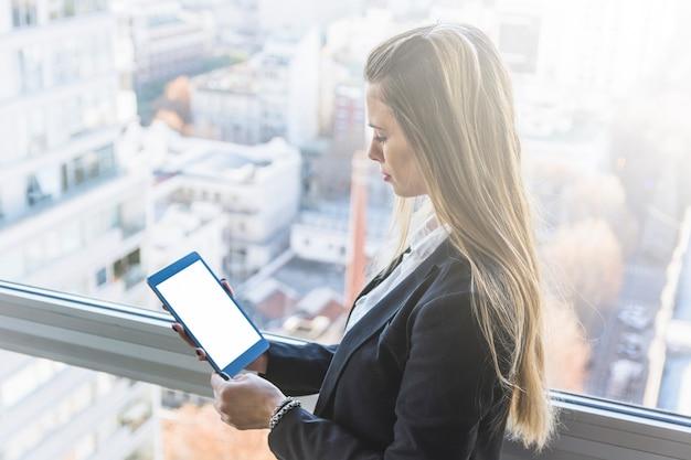Giovane donna bionda guardando smartphone in piedi vicino alla finestra