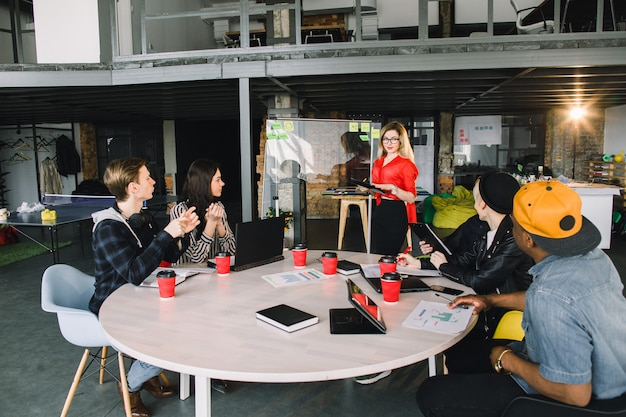 Giovane donna bionda in bicchieri in piedi alla parete di vetro in un incontro con il team multinazionale di lavoratori