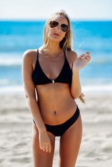 Giovane donna bionda in costume da bagno su una spiaggia tropicale con occhiali da sole aviator.