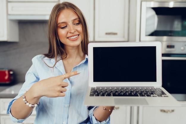 Giovane donna bionda in piedi in kithen e mostrando il computer portatile dello schermo in bianco
