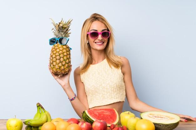 Giovane donna bionda in possesso di un ananas con occhiali da sole