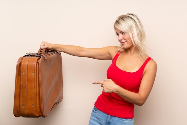 Giovane donna bionda in possesso di una valigetta vintage