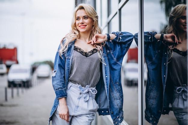 Giovane donna bionda in una giacca di jeans fuori