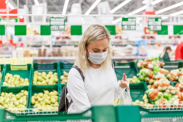 Giovane donna bionda in una maschera medica sceglie i frutti in un grande ipermercato. salute e corretta alimentazione durante una pandemia.
