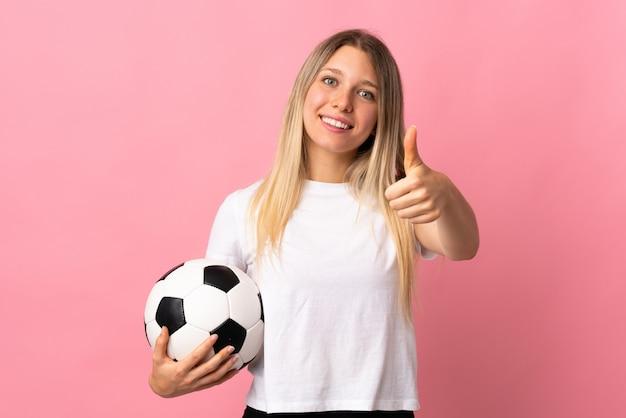 Giovane donna bionda isolata sulla parete rosa con pallone da calcio e con il pollice su