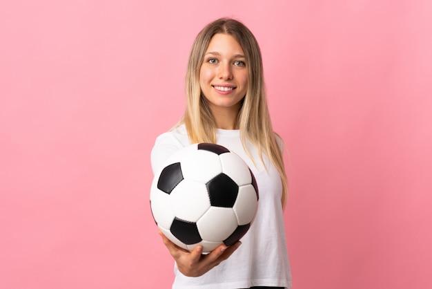 Giovane donna bionda isolata sulla parete rosa con pallone da calcio