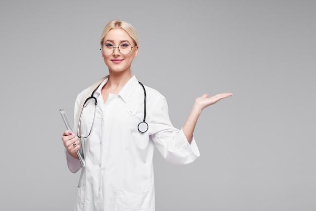 Giovane donna bionda positiva del medico in vetri rotondi, in camice mediche con lo stetoscopio che cattura le note sul pc del ridurre in pani. grigio isolato