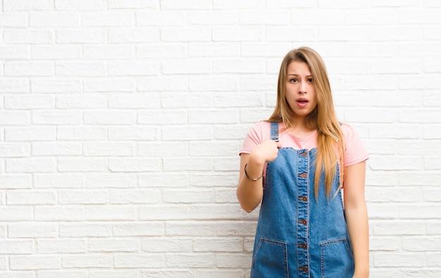 Giovane donna bionda sentirsi confusa, perplessa e insicura, indicando se stessa chiedendosi e chiedendo chi, io? contro il muro di mattoni