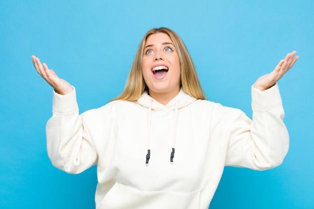 Giovane donna bionda sentirsi felici, stupiti, fortunati e sorpresi, celebrando la vittoria con entrambe le mani in alto sopra il muro