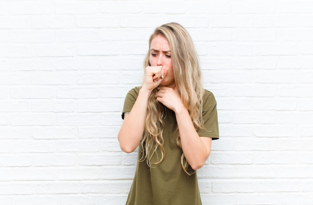 Giovane donna bionda sentirsi male con mal di gola e sintomi influenzali, tossendo con la bocca coperta contro il muro di mattoni
