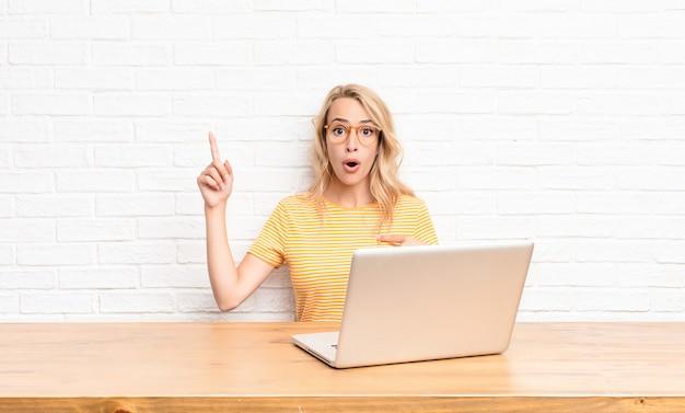 Giovane donna bionda sentirsi orgogliosi e sorpresi, indicando se stessi con fiducia, sentendosi il numero uno di successo usando un computer portatile