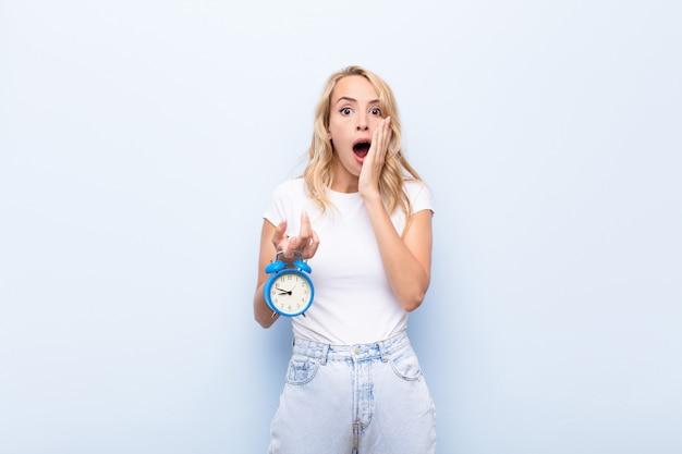 Giovane donna bionda sentirsi scioccata e spaventata, guardando terrorizzata con la bocca aperta e le mani sulle guance in possesso di un orologio
