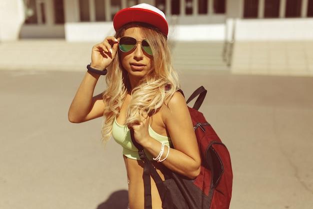 Giovane donna bionda sexy che cammina sulla strada