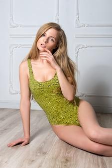 Giovane donna bionda sexy in costume da bagno che posa contro la parete bianca.