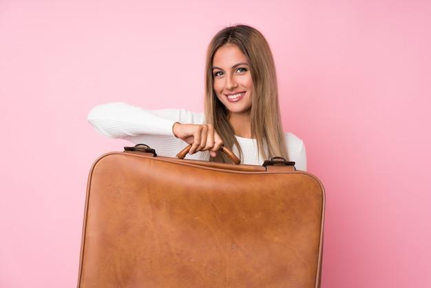 Giovane donna bionda sfondo in possesso di una valigetta vintage