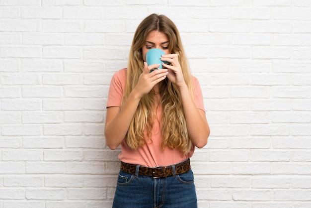 Giovane donna bionda sopra il muro di mattoni bianco che tiene tazza di caffè calda