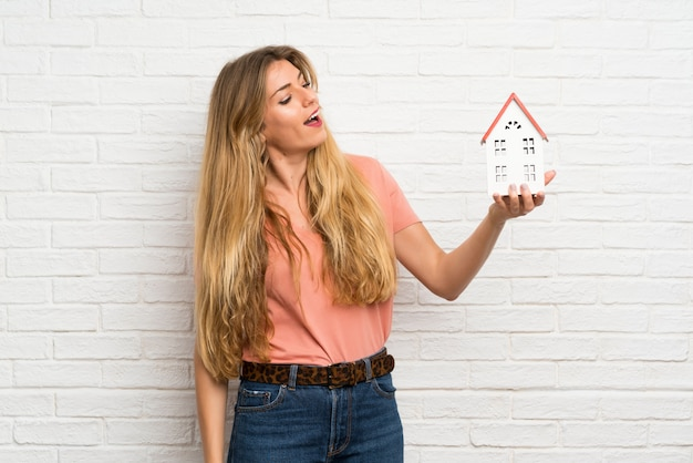 Giovane donna bionda sopra il muro di mattoni bianco che tiene una casetta