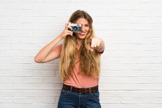 Giovane donna bionda sopra il muro di mattoni bianco che tiene una macchina fotografica