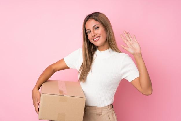 Giovane donna bionda sopra il rosa isolato che tiene una scatola per spostarla in un altro sito e salutare