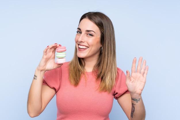 Giovane donna bionda sopra la parete blu isolata che tiene i macarons e il saluto francesi variopinti