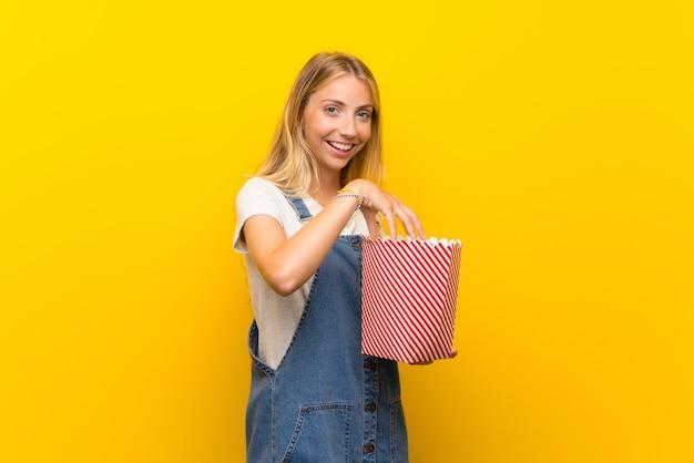 Giovane donna bionda sopra la parete gialla isolata che mangia i popcorn