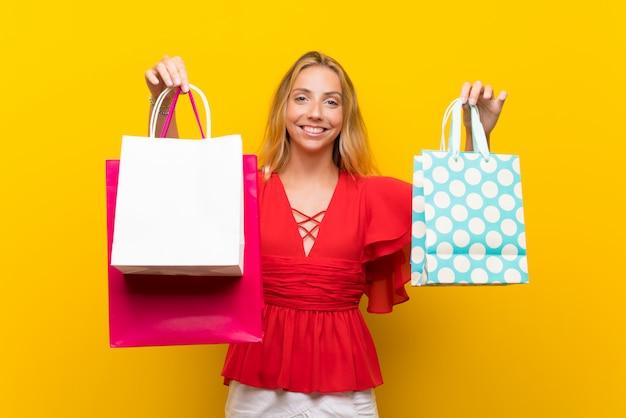 Giovane donna bionda sopra la parete gialla isolata che tiene molti sacchetti della spesa