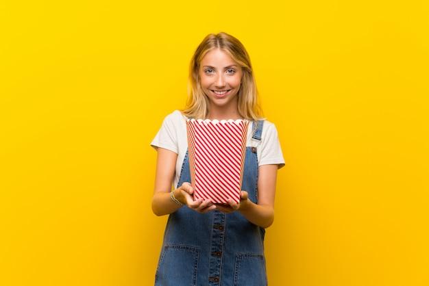 Giovane donna bionda sopra la parete gialla isolata che tiene una ciotola di popcorn