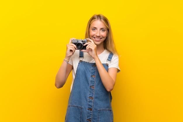 Giovane donna bionda sopra la parete gialla isolata che tiene una macchina fotografica