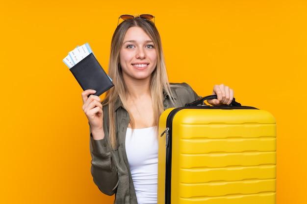 Giovane donna bionda sopra la parete gialla isolata in vacanza con la valigia e il passaporto