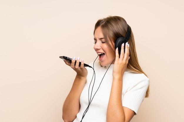 Giovane donna bionda sopra la parete isolata facendo uso del cellulare con le cuffie e cantare