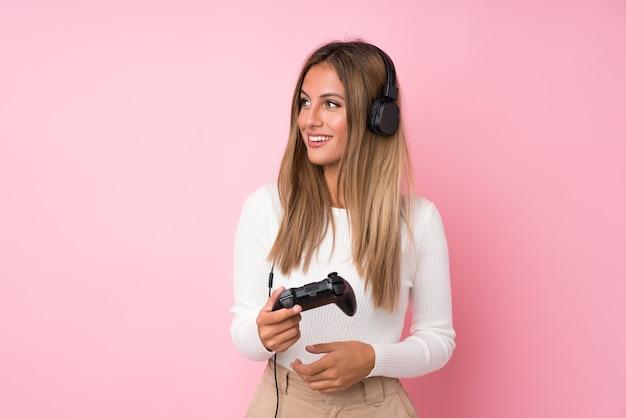 Giovane donna bionda sopra la parete rosa isolata che gioca ai videogiochi