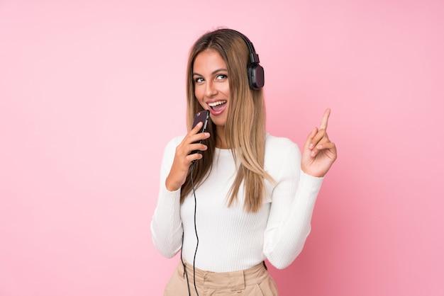 Giovane donna bionda sopra la parete rosa isolata facendo uso del cellulare con le cuffie e cantare